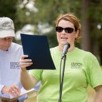 A woman in a bright green ADA25 shirt and sunglasses holds a blue paper up as she reads from it into the microphone. An older gentleman in a baseball cap and a grey ADA25 shirt waits in the background.