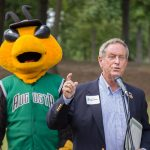 A man in a blue blazer with a white name tag, speaks into a microphone. He has his arms raised as he is mid-sentence. Auggie, the GreenJackets stylized Yellow jacket mascot, stands in the background.