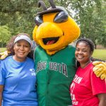 A posed shot of two smiling women in blue and red shirts standing on either side of Auggie, the GreenJackets stylized Yellow jacket mascot.