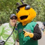 A posed shot of a woman wearing a black ball cap hugging Auggie, the GreenJackets stylized Yellow jacket mascot.