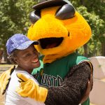 A candid shot of a young lady wearing a blue ball cap hugging Auggie, the GreenJackets stylized Yellow jacket mascot.