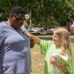 """A young volunteer puts an """"I did the Equality Walk 'n Roll"""" sticker on a woman's shirt following the walk."""