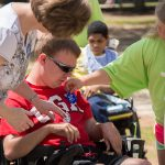 """A young volunteer places an """"I did the Equality Walk 'n Roll"""" blue sticker on a participant's shirt as he sits in his electric wheelchair."""