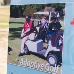 A close-up of the Adaptive Gold informational sign - an image of a golfer with only one leg using the adaptive golf cart to play.