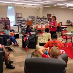 A camp instructor speaks to a group of campers who are sitting in soft chairs during a teaching section. Additional activity stations can be seen beside her.