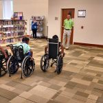 Campers tried a variety of assistive technology during camp, including wheelchairs. This group is mid-race for their wheelchair race.