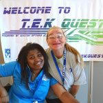 An instructor and a volunteer greet campers and their caregivers in front of the TEK Quest banner.