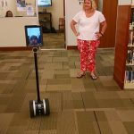 A member of the Tools for Life Team watches one of the robots they brought as a camper navigates it around the library on a a scavanger hunt.