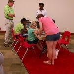 Campers sit at an activity station working with keyboards and text to speech functions.