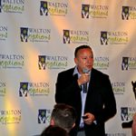Speaker Jeff Eisman holds a microphone as he speaks during the MVP COmmunity Awards while standing in front of the Walton Options backdrop.