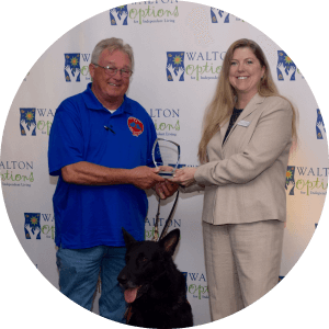 A winner of the MVP Community Awards 2016 is presented with his award by a Walton Options team member in front of the Walton Options Backdrop. The winner also has his service dog next to him.