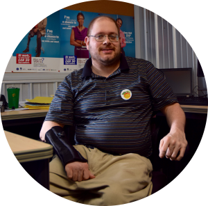 Gentleman in a wheelchair facing the camera at his desk, smiling at the camera.