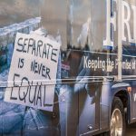 Close up of the back image of the bus - A man holding a sign that reads: Separate is never Equal