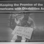 """A close-up of the back of the bus with an image of man in a wheelchair holding a sign that reads """"Buses are for everyone"""". Above the black and white image is the text: Keeping the Promise of the Americans with Disabilities Act."""