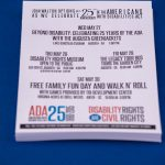 A week full of events to celebrate ADA25! A postcard with the details of all the different ADA25 celebration activities sits on a table with a blue table cloth.