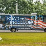 A full length shot of the tour bus. The text on the bus reads: The Road to Freedom, Keeping the promise of the Americans with Disabilities Act, www.roadtofreedom.net. There are images from the ADA advocacy trail on the bus in the background of the text.