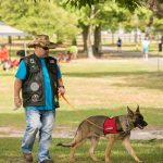 A man with a black vest and cowboy hat holds the leash to his service dog who looks similar to a German Shepherd who has on a red vest.