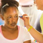 A young woman sits and looks to the side while a volunteer uses a paint brush to work on a cheek painting. The young lady already has a butterfly painted on her other cheek.