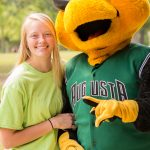 A posed shot of a young lady next to Auggie, the GreenJackets stylized yellow jacket mascot.