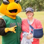 A posed shot of a woman with her arm in a sling holding a tshirt next to Auggie, the GreenJackets stylized yellow jacket mascot.