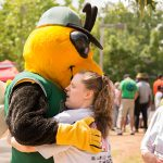 A candid shot of a young lady hugging Auggie, the GreenJackets stylized Yellow jacket mascot.