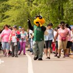 The Augusta GreenJackets Mascot, Auggie, walks in front of a group of people on the walking track at Odell Weeks as they start the Walk n' Roll. The participants vary in age and ability.