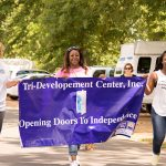 """A group of three women walk on the track holding a blue banner with text """"Tri-Development Center, Inc. Opening Doors to Independence"""""""