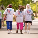 A candid shot of three women at the complete the Walk 'n Roll. All three are wearing the ADA25 Celebration shirts with the logo that can be seen.