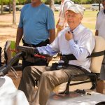 A candid shot of a man sitting in a specially designed golf cart looking at the camera. Another man stands behind him.
