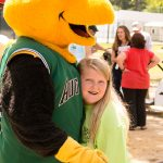 A young girl looks at the camera smiling as she gives Auggie the mascot a hug. Auggie is a stylized version of a yellow jacket wearing an Augusta GreenJackets baseball jersey.
