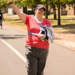 A candid shot of a woman with one arm in a sling and the other arm raised in the air as she finishes the Walk 'n Roll.