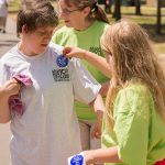 """A candid shot of a woman receiving her """"I did the Equality Walk 'n Roll"""" blue sticker from a young volunteer."""