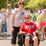 """A woman poses with a man sitting in an electric wheelchair on the track. They both have """"I did the Equality Walk 'n Roll"""" blue stickers on. There are other walkers behind them receiving their stickers from volunteers."""