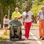 A group of older members of the community walk with an older man in a wheelchair on the track during the Walk n' Roll. A young woman is with them assisting two of the men.