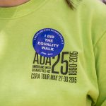 """A close up of an ADA25 CSRA Tour shirt with a blue sticker with white text: Americans with Disabilities Act, I did the Equality Walk 'n Roll"""""""