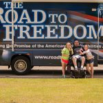 A man sits in his electric wheelchair with two girls standing on either side of him, looking at the camera smiling. All three are posed in front of the Road to Freedom Tour Bus