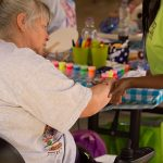 An older woman sits in her electric wheelchair while a volunteer holds her arm and paints a design on her forearm