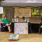 Three ladies sit behind tables with information about the Aiken Board of Disabilities. They are sitting under a brown pop-up tent with a banner at the back of the tent with contact info for ACBD.