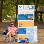 A woman sits in a camping chair next to a roll-up banner with information about Mental Health America and what they do