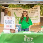 """One of the vendors from the ADA25 Family Fun Day - A woman in a green tshirt stands behind a table with a green table cloth with text """"Family Pharmacy"""" on it in white. There is also a sign sitting on the table with text """"Free Hearing Screens"""". The table is under a pop-up tent with a Family Pharmacy banner hanging on the back."""