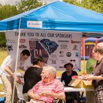 During the ADA25 Family Fund Day - a photo of the drink and snacks table with people in line collecting pates, food and drinks. The ADA25 CSRA banner hangs on the back-side of the blue pop-up tent set-up over the table.