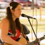During the ADA25 Family Fun Day, a woman is playing a guitar and singing into a microphone. She appears to be mid-song.