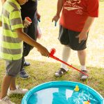A boy holding a snow cone lowers a plastic fishing rod in an attempt to catch a rubber duck from a small pool filled with water. A young man waits his turn behind the pool.