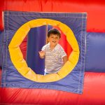 A young boy smiles and looks through the opening of an inflatable bouncy castle during the ADA25 Family Fun Day