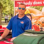 A man smiles at the camera as he stands behind the bags of pizza offered for lunch during the ADA25 Family Fun Day. A banner with pizza is behind him.
