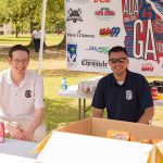 Two men sit at the drinks table during the ADA25 Family Fun Day. They are looking at the camera smiling with the ADA25 CSRA Tour banner behind them.