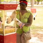 A volunteer scoops popcorn out of an old fashion popcorn machine into a small paper bag.