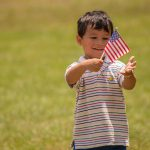 A young boy holds a small American Flag on a stick while he plays in the park.