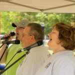 A candid shot of a singing trio - the closest a woman and the two others men. They are all facing to the left and singing into microphones under a pop-up tent.
