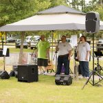 A trio of singers, two men and a woman, stand at microphones under a brown, pop-up tent singing. All three have ADA25 celebration tshirts on. Speakers can be seen in front of the tent facing the park.